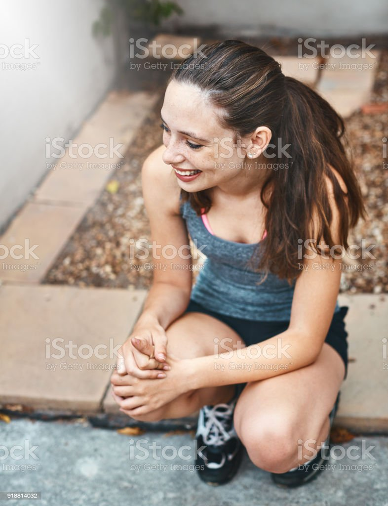 Cute, smiling girl sitting on stone slab outdoors stock photo