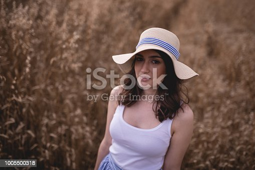 istock Cute smiling girl with a hat in a wheat field 1005500318