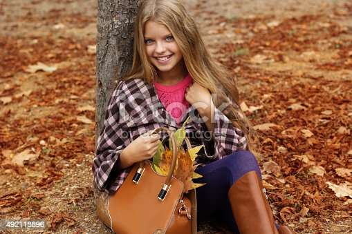 istock Cute smiling girl with bag full of autumn leaves 492118896