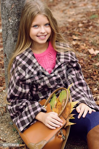 istock Cute smiling girl with bag full of maple leaves 492118916