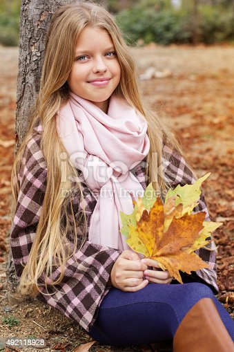 istock Cute smiling girl with bag full of maple leaves 492118928