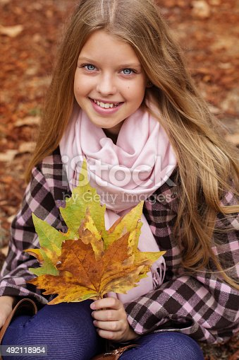 istock Cute smiling girl with maple leaves in hands 492118954