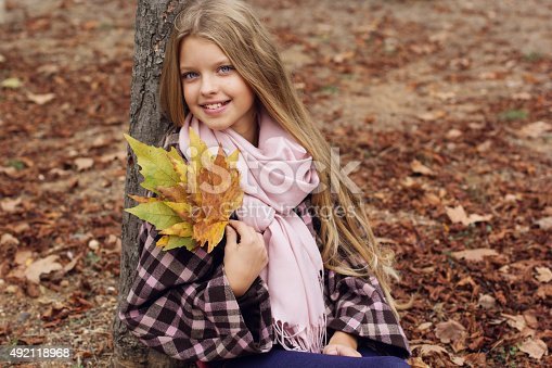 istock Cute smiling girl with maple leaves in hands 492118968
