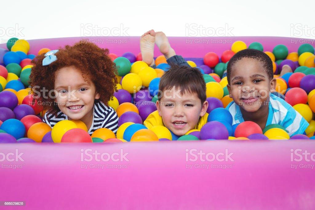 Enfants souriants mignons dans la piscine à balles éponge - Photo