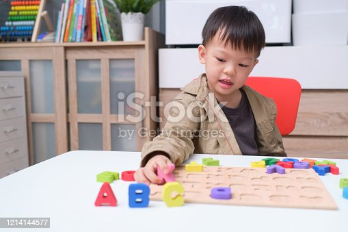 Cute smiling kindergarten boy playing with alphabet blocks, Asian children learning English with wooden educational abc toy puzzle for kids, Teach young kids English at home concept