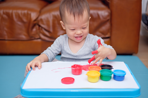 1042756824 istock photo Cute smiling little Asian 18 months / 1 year old toddler baby boy child finger painting with hands and watercolors 929708920