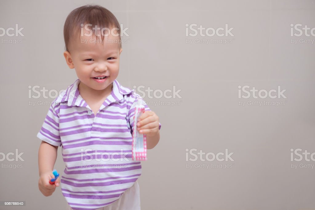 Cute smiling little Asian 18 months / 1 year old toddler boy child wearing purple shirt holding toothbrush and learn to brushing teeth stock photo