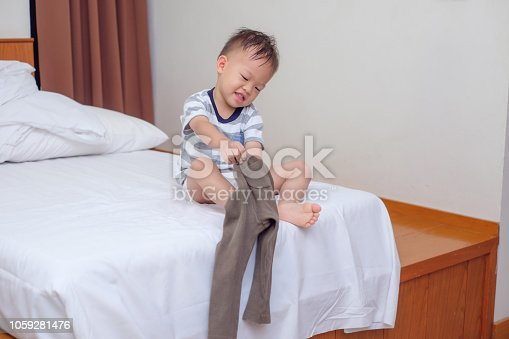 istock Cute smiling little Asian 2 years old toddler boy child sitting in bed concentrate on putting on his pants 1059281476