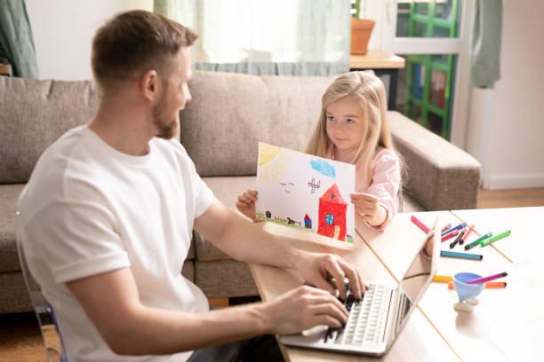 Nette lächelnde kleine Tochter zeigt Bild mit Farbstiften zu ihrem Vater gezeichnet – Foto