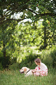 istock Cute smiling little girl hugging and  ironing labrador in the summer park 1137370765