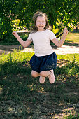 Cute smiling little girl in white t-shirt and dark blue skirt jump outdor in field in sunset. Activities with children summer outdoors. Having fun. Vertical.