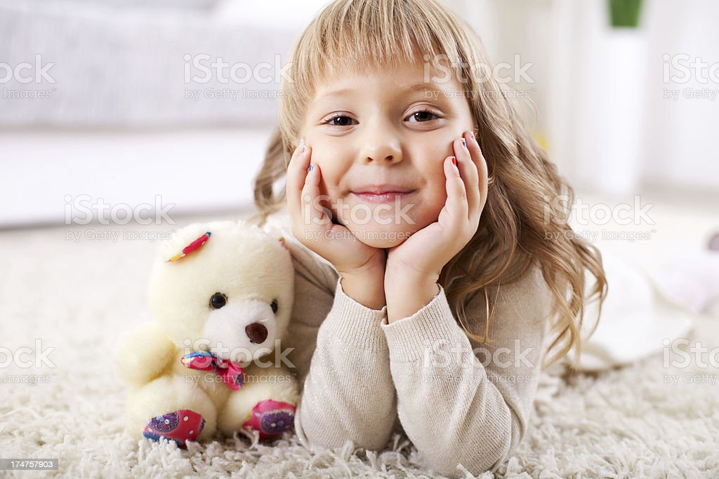 Cute smiling little girl lying on the carpet. royalty-free stock photo