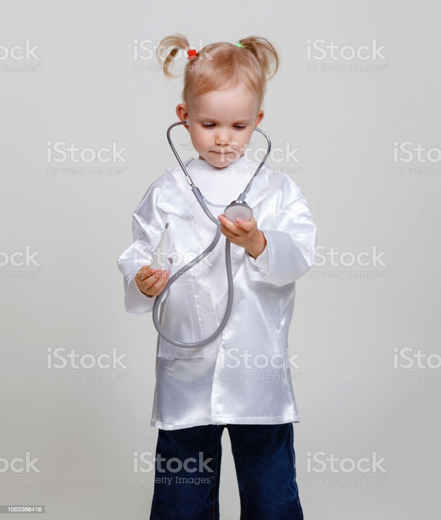 Cute smiling little girl with stethoscope and thermometer in doctor costume. Funny 2-3 years old girl, copy space, gray background stock photo