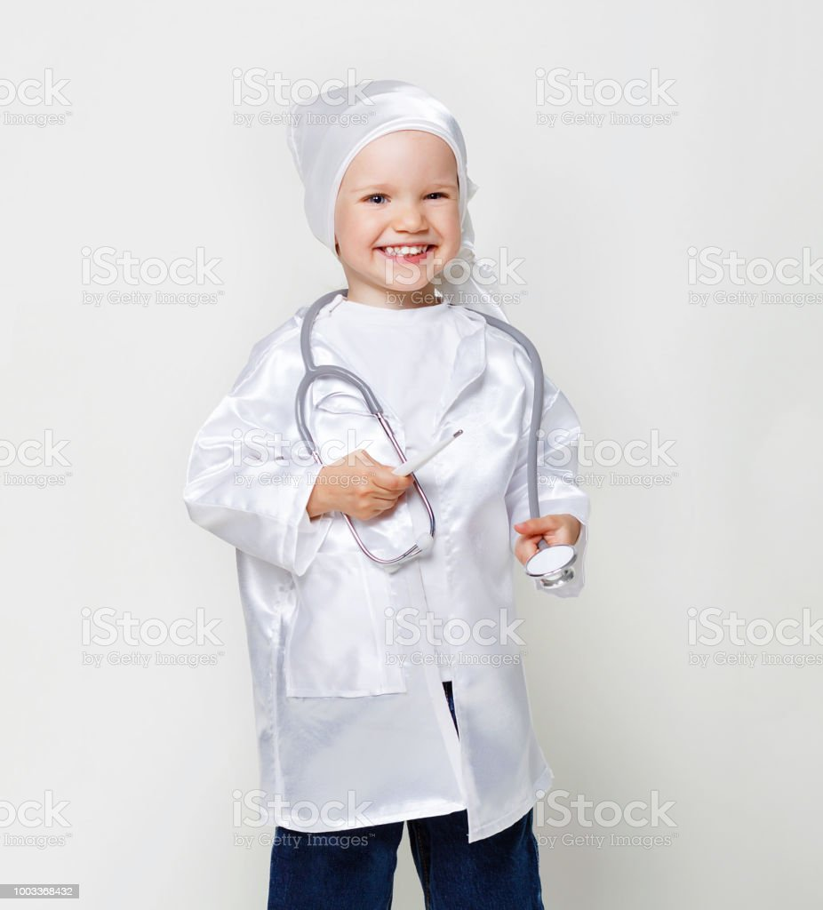 Cute smiling little girl with stethoscope and thermometer in doctor costume. Funny 2-3 years old girl wide smile showing teeth. Copy space, gray background stock photo