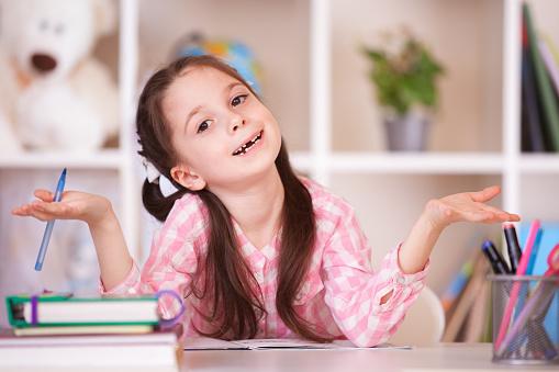 Cute smiling school girl shrugs shoulders. Children education, self isolation, coronavirus outbreak social distancing or homeschooling. Online studying concept.