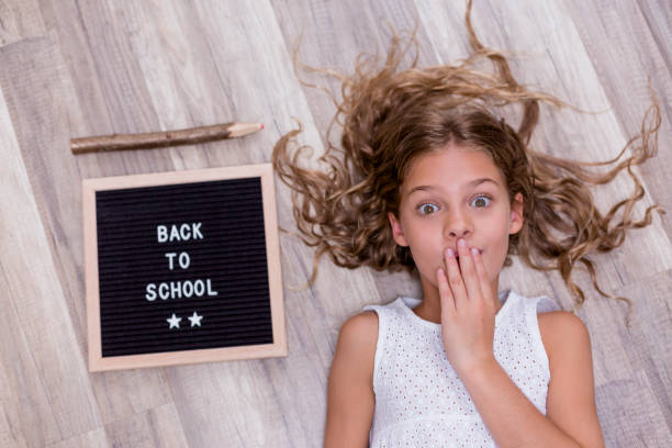 Cute smiling schoolgirl lying on the floor with letter board and smiling. Back to school concept. Family lifestyle indoors. Surprise stock photo