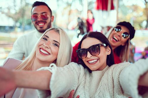Cute Smiling Selfie By Friends Enjoying Carousel Ride In The Park