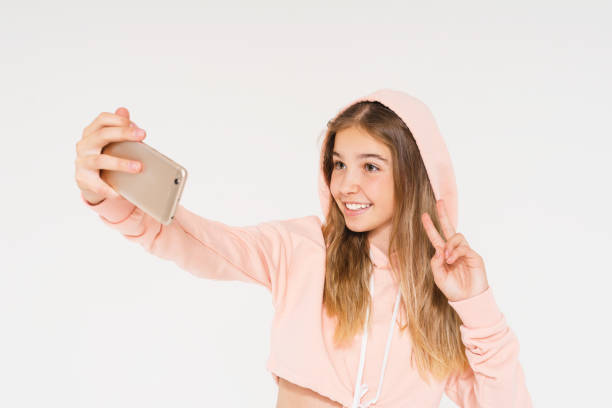 cute smiling teen girl in pink hoodie taking selfie on smartphone isolated on the white background - phone 12 hand white background imagens e fotografias de stock