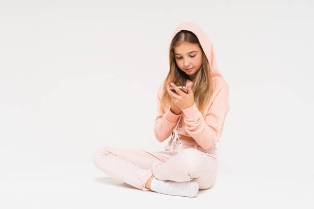 cute smiling teen girl in pink hoodie using smartphone isolated on the white background - phone 12 hand white background imagens e fotografias de stock