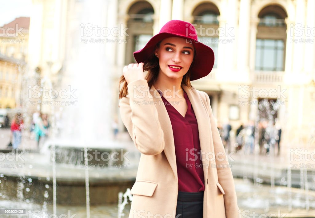Cute smiling woman in coat and on street tourist town - Royalty-free Adult Stock Photo