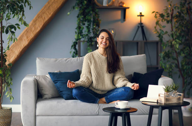 Cute smiling woman is doing yoga at home stock photo