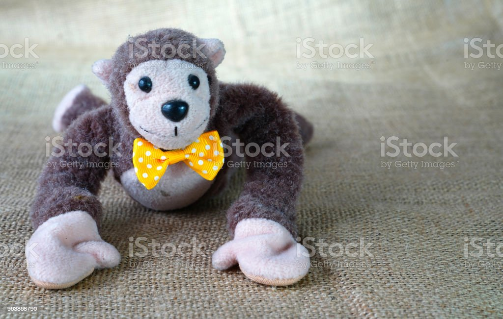 Cute soft toy monkey with yellow bow tie lying on floor - Royalty-free Animal Stock Photo