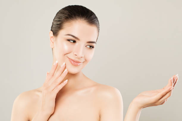 Cute Spa Model Woman with Healthy Skin and Empty Open Hand. Spa Beauty, Facial Treatment and Cosmetology Concept stock photo