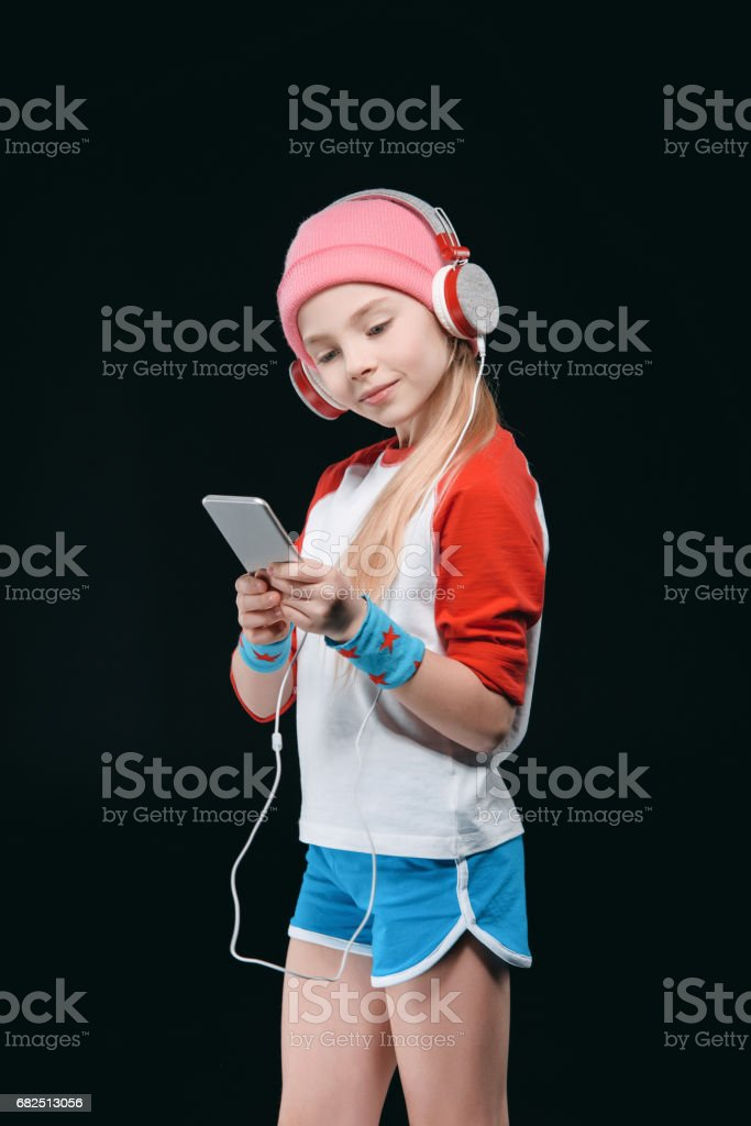 Cute sporty girl in headphones using smartphone isolated on black, activities for children concept foto stock royalty-free
