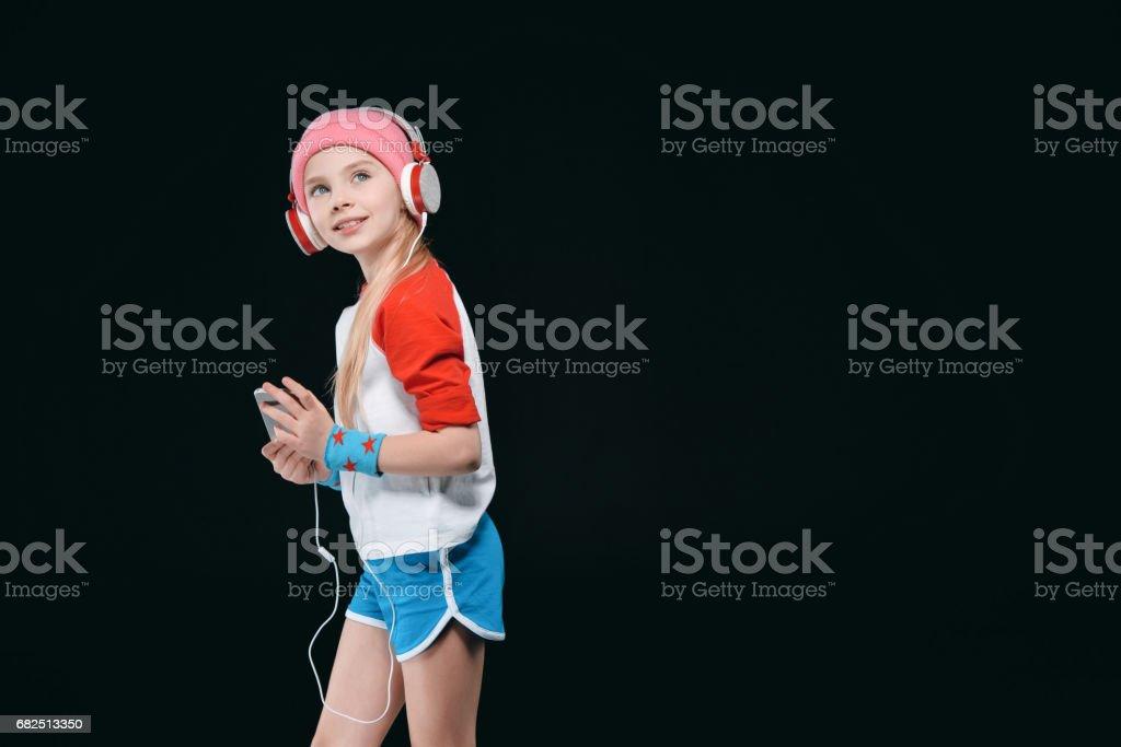 Cute sporty girl in headphones using smartphone isolated on black, activities for children concept Стоковые фото Стоковая фотография