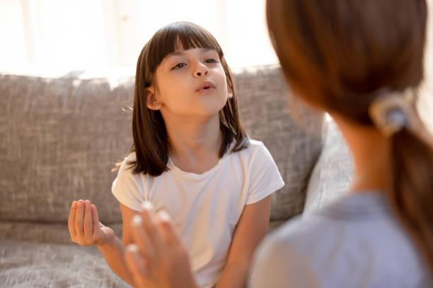 niedliches stotterndes kindermädchen, das übungen mit sprachtherapeuten macht - lautbildungsspiele stock-fotos und bilder
