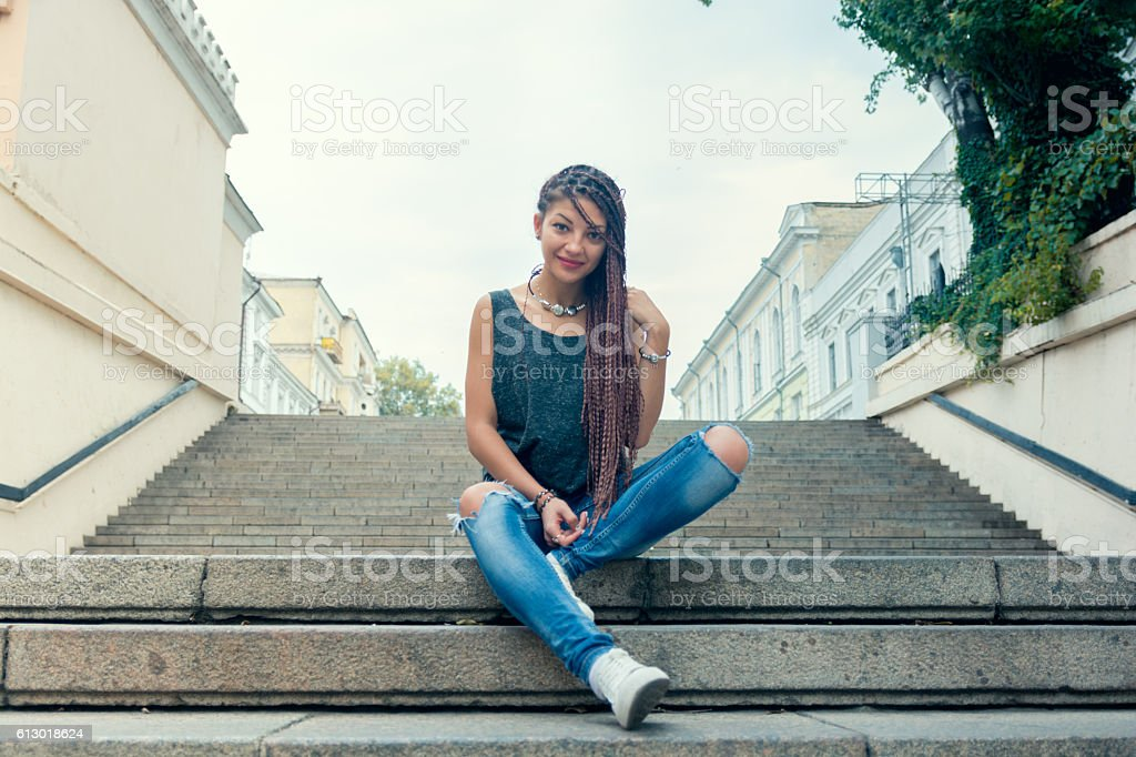 Cute stylish woman sitting on stairs and smile stock photo