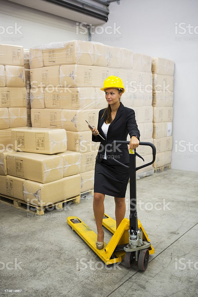 Cute supervisor in a warehouse on pallet truck royalty-free stock photo