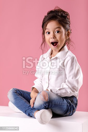 istock Cute surprised little girl in white shirt with hairstyle 1125666040