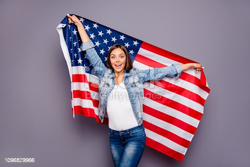 istock Cute sweet lovely excited smiling lady emigrant worker  holding USA american flag behind back, isolated over grey background 1096829966