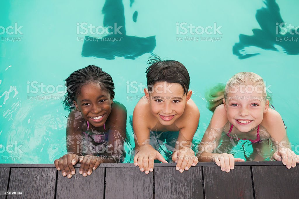 Cute swimming class in pool with coach stock photo