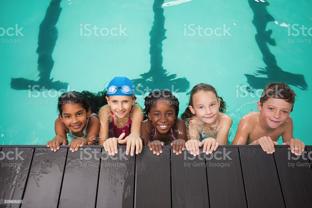 Cute swimming class smiling at camera stock photo
