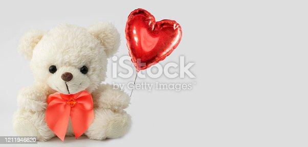Cute teddy bear holds a heart ball. Valentine with a bear.