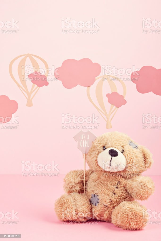 Cute teddy bear over the pink pastel background with clouds and...