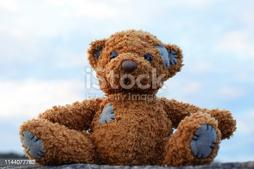 Cute little brown teddy bear plush toy sitting on stone outdoors on blue sky background.