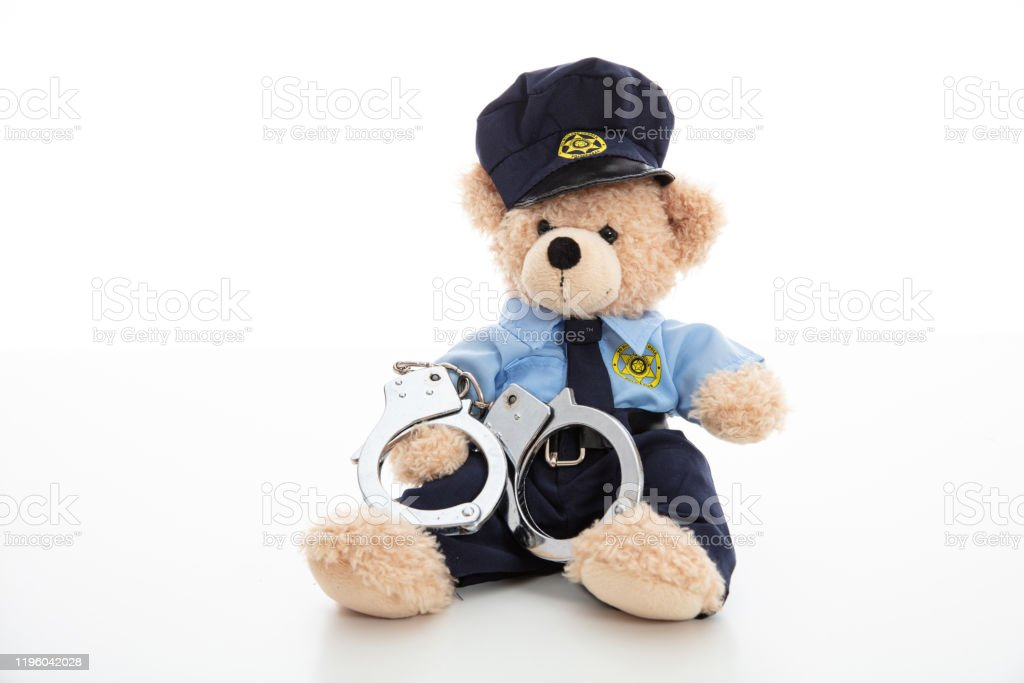 Cute teddy in policeman uniform and handcuffs isolated against white background Police and arrest concept. Cute teddy bear in police officer uniform and handcuffs isolated against white background Arrest Stock Photo