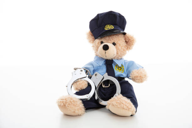 Cute teddy in policeman uniform and handcuffs isolated against white background Police and arrest concept. Cute teddy bear in police officer uniform and handcuffs isolated against white background arrestment stock pictures, royalty-free photos & images