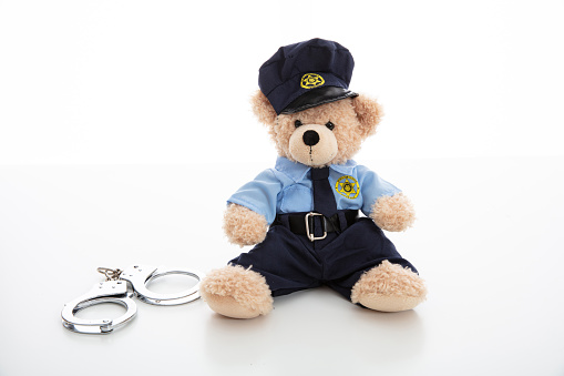 Cute Teddy In Policeman Uniform And Handcuffs Isolated Against White Background Stock Photo - Download Image Now