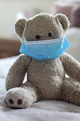 Cute well loved teddy sitting on the edge of children's bedroom. Teddy is smiling under his blue face protection. Protection against the covid-19 coronavirus pandemic.
