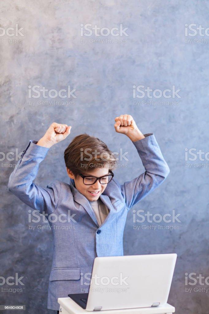 可愛的青少年男孩與筆記本電腦和手對牆 - 免版稅互聯網圖庫照片