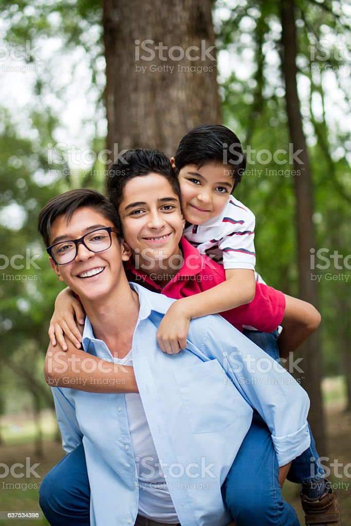 Cute teenage boy carrying his brothers on his back - foto de stock