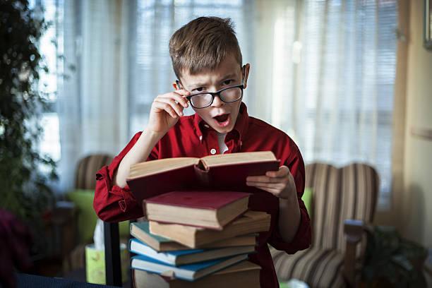 cute teenage boy with eyeglasses reading a book - haushaltsbuch führen stock-fotos und bilder