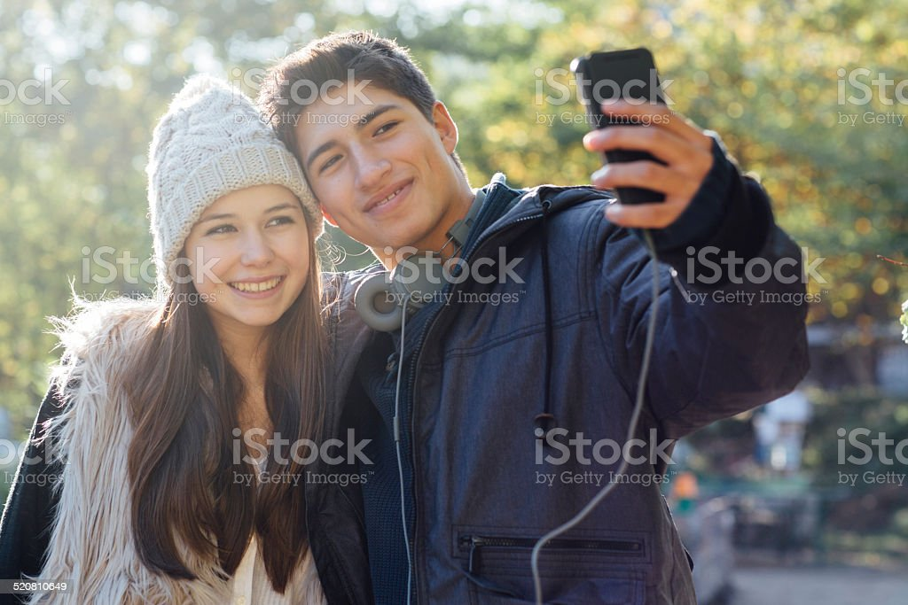 cute teenage couple takes a selfie on nature background stock photo