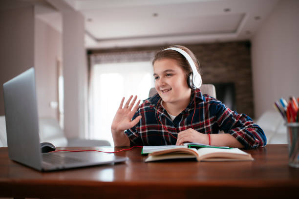 Cute teenage girl making a video call via laptop stock photo stock photo