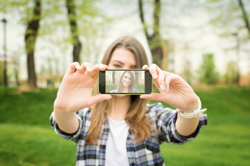 Cute teenage girl taking a selfie photograph with smart phone