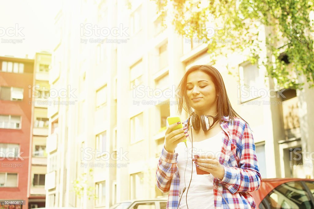 Cute teenage hipster girl with smartphone in urban environment stock photo